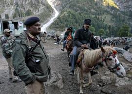 An Indian police officer keeps guard as Hindu pilgrims on horses proceed to reach the holy cave of Lord Shiva in Amarnath, 141 km (87 miles) southeast of Srinagar (File).