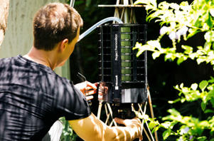 Researcher Ethan Jackson places the Project Premonition mosquito trap in the wild