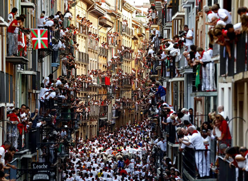 Slide 1 dari 30: Sanfermines 2017 in Pamplona, Spain - 07 Jul 2017 People observe from their balconies while bulls from the bull ranch Cebada Gago chase runners or 'mozos' during the first bull run of Sanfermines 2017 in Pamplona, Navarra, northern Spain, 07 July 2017. The festival, locally known as Sanfermines, is held annually from 06 to 14 July in commemoration of the city's patron saint San Fermin.