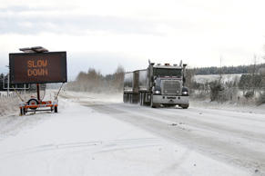 Road singage is placed roadside to warn traffic of the icy conditions as snow falls (file)