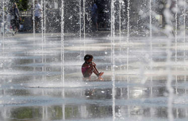 A child sits in a water fountain during a warm summer day in Nice, southeastern France on July 12, 2017.