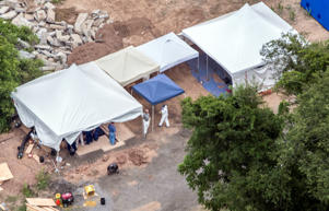 In this aerial photo, investigators work under tents as they search for clues in the disappearance of four men, Thursday, July 13, 2017 in Solebury, Pa. Cosmo DiNardo, 20, a jailed man who has been the focus of an investigation into the disappearances of the four men, admitted on Thursday that he killed them and agreed to plead guilty to four murder counts, his attorney said.