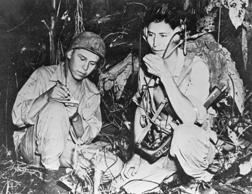 Two U.S. Marine Navajo 'code talkers', signalmen who used a slightly modified version of their native language, send a radio signal during the battle of Bougainville in 1943. The Japanese were never able to break this code.
