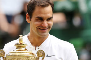 Roger Federer celebrates victory with the Wimbledon trophy.