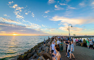 Crowd of people gathered at St Kilda breakwater to watch penguins after sunset on a warm summer evening