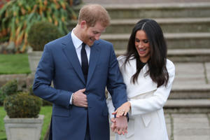 Britain's Prince Harry stands with his fiancée US actress Meghan Markle as she shows off her engagement ring whilst they pose for a photograph in the Sunken Garden at Kensington Palace in west London on November 27, 2017, following the announcement of their engagement. Britain's Prince Harry will marry his US actress girlfriend Meghan Markle early next year after the couple became engaged earlier this month, Clarence House announced on Monday.