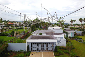 "A power line tower downed by the passing of Hurricane Maria lies on top of a house in San Juan, Puerto Rico on November 7, 2017.  The Center for Puerto Rican Studies at Hunter College in New York estimated in a report released last month that about 114,000 to 213,000 Puerto Rican residents will leave the island annually ""as a result of Hurricane Maria."""
