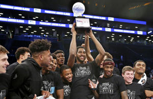 Texas A&M center Tonny Trocha-Morelos raises the trophy after he and his teammates celebrate defeating Penn State in an NCAA college basketball game to win the Legends Classic tournament, Tuesday, Nov. 21, 2017, in New York. Texas A&M defeated Penn State 98-87 to win the two-day, two-round tournament. (AP Photo/Kathy Willens)