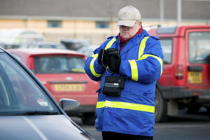 Private car park attendant taking details of a car
