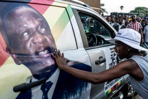 A supporter of Emmerson Dambudzo Mnangagwa touches an image of the politician glued on a SUV at the ZANU-PF headquarter in Harare, on Nov.22. Zimbabwe's former vice president Emmerson Mnangagwa flew home on November 22 to take power after the resignation of Robert Mugabe put an end to 37 years of authoritarian rule. Mnangagwa will be sworn in as president at an inauguration ceremony on Nov. 24, officials said.