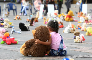 A child hugs a stuffed toy during a demonstration organized by the Aldeas Infantiles SOS Colombia against child sexual assault, in Bolivar Square in Bogota, Colombia, 20 November 2017.