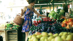 a woman standing in front of a fruit stand: Your Mood Depends on What You Eat