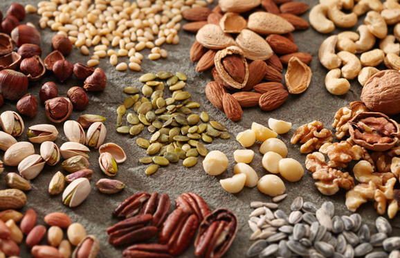 Lysbilde 1 av 15: A variety of healthy and organic nuts and seeds in piles on a slate surface.