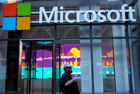 A man passes a Microsoft office in New York on October 6, 2015. Microsoft introduced a pair of big-screen smartphones and a laptop during an event in New York on Tuesday. The company unveiled the Surface Book, a laptop with 13.5-inch detachable touchscreen, the Surface Pro 4 tablet and the Lumia 950 and 950 XL smartphones, which feature displays measuring over 5 inches. The Surface devices launch later this month, while the Lumias arrive in November.
