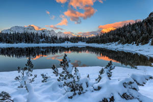 The colors of dawn on the snowy peaks and woods reflected in Lake Palù Malenco Valley Valtellina Lombardy Italy Europe