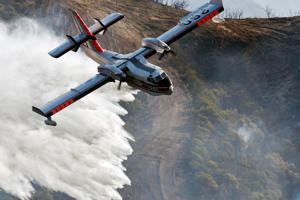 In this photo provided by the Santa Barbara County Fire Department, a Bombardier 415 Super Scooper makes a water drop on hot spots along the hillside east of Gibraltar Road in Santa Barbara, Calif., Sunday morning, Dec. 17, 2017. Wind gusts of up to 52 mph have been recorded in the area using a hand held weather device. The Office of Emergency Services announced the orders Saturday as Santa Ana winds pushed the fire close to the community. The mandatory evacuation zone is now 17 miles long and up to 5 miles wide, extending from coastal mountains northwest of Los Angeles to the ocean. Winds in the foothill area are hitting around 30 mph, with gusts up to 60 mph. (Mike Eliason/Santa Barbara County Fire Department via AP)