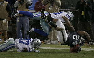 Oakland Raiders running back Marshawn Lynch (24) is tackled between Dallas Cowboys cornerback Jourdan Lewis (27) and middle linebacker Anthony Hitchens during the second half of an NFL football game in Oakland, Calif., Sunday, Dec. 17, 2017. (AP Photo/Eric Risberg)