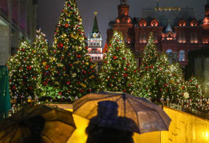 MOSCOW, RUSSIA - DECEMBER 17, 2017: People with umbrellas in the rain at the entrance to the Moscow underground in Manezhnaya Square, with Christmas trees behind; the warmest December day in Moscow has been recorded as the temperatures reached +4 degrees Celsius in the morning, the highest recorded December temperature in the Russian capital since 1879. Valery Sharifulin/TASS (Photo by Valery Sharifulin\TASS via Getty Images)