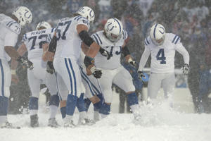 Indianapolis Colts players try to clear a space in the snow to make space for an after point during the second half of an NFL football game against the Buffalo Bills on Dec. 10, 2017, in Orchard Park, N.Y.