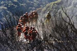 In this photo provided by the Santa Barbara County Fire Department, CAL FIRE Inmate Firefighting Hand Crew members hike through the charred landscape on their way to work east of Gibraltar Road above Montecito, Calif., Tuesday, Dec. 19, 2017. Officials estimate that the fire will grow to become the biggest in California history before full containment, expected by Jan. 7.