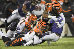Baltimore Ravens running back Alex Collins (34) is stopped by Cincinnati Bengals defensive end Jordan Willis (75) and free safety George Iloka (43) during the first half of an NFL football game in Baltimore, Sunday, Dec 31, 2017.
