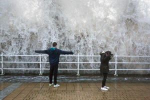 Children stand on the seafront as a wave crashes over the sea wall in Aberystwyth in west Wales