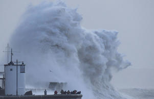 People view large waves and high winds associated with Storm Eleanor as they hit the lighthouse and seawall at Porthcawl in south Wales.