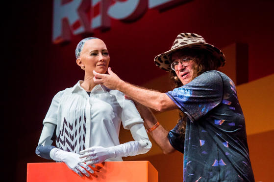 สไลด์ 1 จาก 21: Chief scientist of Hanson Robotics, Ben Goertzel (R), describes to the audience what 'Sophia the Robot' (L) is made of during a discussion about the future of humanity in a demonstration of artificial intelligence (AI) by Hanson Robotics at the RISE Technology Conference in Hong Kong on July 12, 2017. Artificial intelligence is the dominant theme at this year's sprawling RISE tech conference at the city's harbourfront convention centre, but the live robot exchange took the AI debate to another level. / AFP PHOTO / ISAAC LAWRENCE (Photo credit should read ISAAC LAWRENCE/AFP/Getty Images)