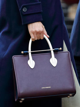 "Slide 1 of 10: Markle defied royal tradition in November when she attended her first official engagement with Prince Harry carrying a burgundy and navy Strathbury tote bag.According to royal etiquette expert William Hanson, royal women are encouraged to carry clutches, rather than purses with straps, to deter people from reaching to shake their hands.Per tradition, people are only allowed to shake royal family members' hands if they extend their hand first—not the other way around. This is why Kate Middleton is frequently spotted with purses instead of handbags.'It is protocol that you do not extend your hand to any member of the royal family (blood royal or those who have married into the family) unless their hand extends first,"" Hanson told The Daily Mail."