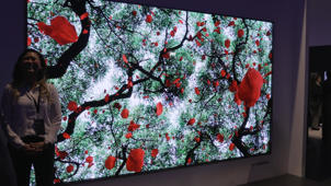 person standing in front of a television: CES 2018: TVs Get Smarter and Brighter in 2018