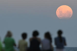 NAPIER, NEW ZEALAND - JANUARY 31: Crowds gather on the Marine Parade Beach to watch the moon rise on January 31, 2018 in Napier, New Zealand. A Super Blue Blood Moon is the result of three lunar phenomena happening all at once: not only it it the second full moon in January, but the moon will also be close to its nearest point to Earth on its orbit, and be totally eclipsed by the Earth's shadow. The last time these events coincided was in 1866, 152 years ago. (Photo by Kerry Marshall/Getty Images)