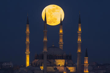 EDIRNE, TURKEY - JANUARY 31: 'Super blue blood moon' rises over Selimiye Mosque in Edirne District of Turkey on January 31, 2018. The 'Super Blue Blood Moon' is a rare 'lunar trifecta' event in which the moon is at its closest to the earth, appearing bigger and brighter than usual and is simultaneously a 'blue moon', the second full moon in the same month, and in total lunar eclipse or 'blood moon'. For the first time in 152 years, a supermoon, blue moon, and total lunar eclipse coincide. (Photo by Gokhan Balci/Anadolu Agency/Getty Images)