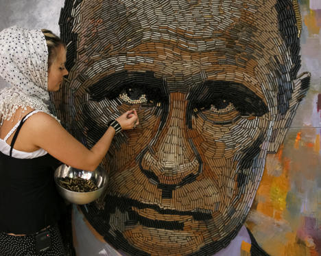 "Slide 3 of 27: Ukrainian artist Dariya Marchenko works on a portrait of Russian President Vladimir Putin named ""The Face of War"" which is made out of 5,000 cartridges brought from the frontline in eastern Ukraine, in Kiev, July 23, 2015. The portrait will be presented along with a novel which will tell personal stories of six people involved in this project including Daria's own story and stories of people who helped her to collect shells from the frontline. Daria Marchenko calls her art approach philosophic symbolism where every element has its hidden meaning. In her works cartridges mean human's life that was brutally ended. Picture taken July 23, 2015."