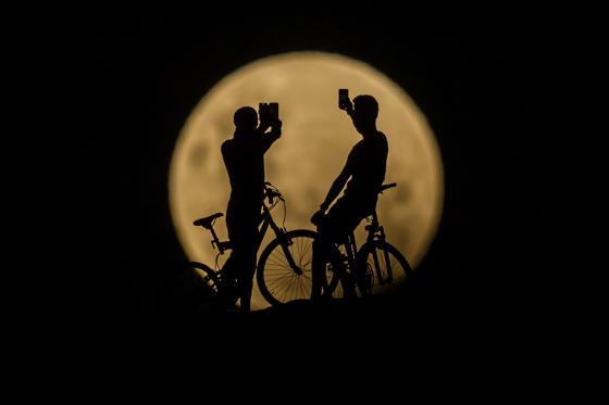 Slide 1 de 50: PERTH, AUSTRALIA - JANUARY 31: Photo Illustration showing people with bicycles taking photos of the Super moon on January 31, 2018 in Lancelin, Australia. Last seen from Australia in December 1983, a Super Blue Blood Moon is the result of three lunar phenomena happening all at once. Not only is it the second full moon in January, but the moon will also be close to its nearest point to Earth on its orbit, and be totally eclipsed by the Earth's shadow. (Photo by Paul Kane/Getty Images)