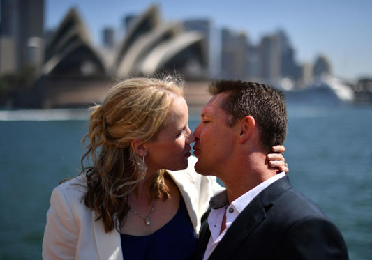 Slide 1 of 21: A newlywed couple kisses aboard the Manly ferry in front of Australia's Opera House in Sydney on February 14, 2018 during an event organised by the Registry of Births, Deaths and Marriages (BDM) as a Valentines Day promotion. / AFP PHOTO / SAEED KHAN (Photo credit should read SAEED KHAN/AFP/Getty Images)