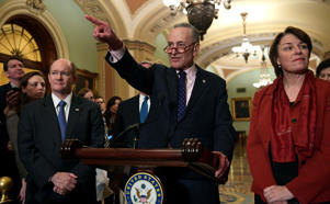 Senate Minority Leader Sen. Chuck Schumer of N.Y., center, calls on a reporter on Capitol Hill in Washington, Tuesday, Feb. 13, 2018, following the weekly Democratic policy luncheon.