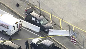 In this image made from video and provided by WUSA TV-9, authorities investigate the scene of a shooting at Fort Meade, Md. on Wednesday, Feb. 14, 2018. A suspect has been held, taken from the black SUV that stopped at barrier after a shooting outside National Security Agency