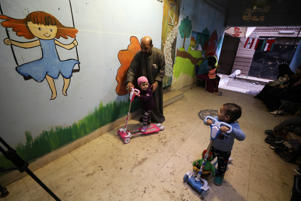 Zaza Ogaz, 50, plays with Yehia, 2, and Retaj, 2, who were diagnosed with cancer, at Ogaz's free housing for patients receiving treatment at a nearby cancer hospital, in Cairo, Egypt February 12, 2018.