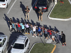 People are brought out of the Marjory Stoneman Douglas High School after a shooting at the school that reportedly killed and injured multiple people on Feb. 14, 2018 in Parkland, Fla. Numerous law enforcement officials continue to investigate the scene.