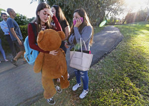 Students wait to be picked up after a shooting at Marjory Stoneman Douglas High School in Parkland, Fla., Wednesday, Feb. 14, 2018. A shooter opened fire at the Florida high school Wednesday, killing people, sending students running out into the streets and SWAT team members swarming in before authorities took the shooter into custody.