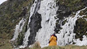 a person standing on a rocky hill: Incredible video shows supernatural beauty of frozen waterfall