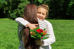 Girl gives her mum a bouquet of flowers for Mother's Day.