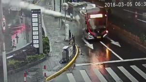 a close up of a street: Pillar smashes bus after being blown off a building
