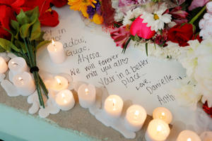 A handwritten note to a lost friend is surrounded by candles and flowers at a candlelight vigil the day after a shooting at Marjory Stoneman Douglas High School in Parkland, Florida, U.S.