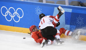 Russia's Maria Batalova and Canada's Jillian Saulnier (R) fall in the women's semi-final ice hockey match between Canada and the Olympic Athletes from Russia during the Pyeongchang 2018 Winter Olympic Games at the Gangneung Hockey Centre in Gangneung on February 19, 2018.   / AFP PHOTO / JUNG Yeon-Je
