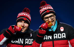 Canada's gold medallists Justin Kripps and Alexander Kopacz bite their medals on the podium during the medal ceremony for the 2-man bobsleigh at the Pyeongchang Medals Plaza during the Pyeongchang 2018 Winter Olympic Games in Pyeongchang on February 20, 2018.