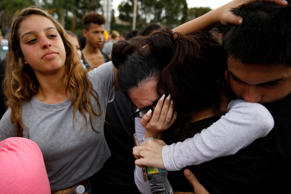 Paola Quitero (C), a student from Olympic Heights Community High School grieves with friends at Marjory Stoneman Douglas High School, during a protest, following a mass shooting in Parkland, Florida, U.S., February 20, 2018.