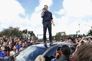 Majory Stoneman High School student Cameron Kasky addresses area High Schoolstudents as they rally at Marjory Stoneman Douglas High School after participating in a county wide school walk out in Parkland, Florida on February 21, 2018.  A former student, Nikolas Cruz, opened fire at Marjory Stoneman Douglas High School leaving 17 people dead and 15 injured on February 14.