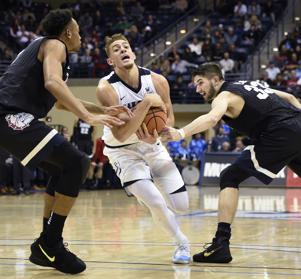 San Diego forward Isaiah Pineiro (0) holds on to the ball as he drives between Gonzaga forward Johnathan Williams, left, and Killian Tillie (33) on Feb. 22, in San Diego. Gonzaga won 77-72.