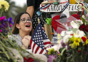 Ariana Gonzalez is overcome with emotion as she visits a cross setup for her friend, football coach Aaron Feis, at the memorial in front of Marjory Stoneman Douglas High School as teachers and staff are allowed to return to the school for the first time since the mass shooting on campus on Feb. 23,  in rkland, Florida.